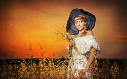 Young woman standing on a wheat field with sunrise on the background Stock Images