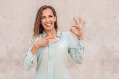 Young woman standing on wall looking camera happy showing ok gesture royalty free stock image