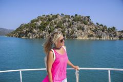 Young woman standing on yacht at sunny day and looking to a sea royalty free stock photo