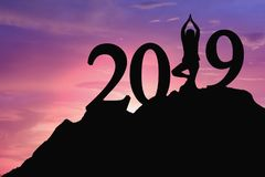 Young woman standing, yoga on mountain, for 2019 new year with s royalty free stock image