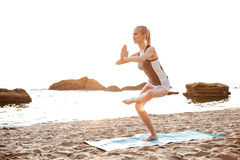 Young woman standing in yoga pose on one leg Royalty Free Stock Photography