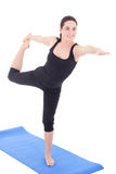 Young woman standing in yoga pose on rubber mat isolated on whit Stock Photography