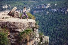 Young woman standing in yoga pose on top of cliff Royalty Free Stock Photos