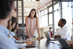 Young woman stands addressing colleagues at business meeting Royalty Free Stock Photos