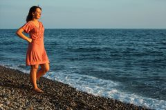 Young woman stands ashore of sea Stock Images
