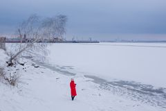 Young woman stands on bank of frozen river and looks at pictorial landscape stock photography