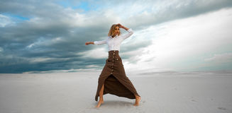 Young woman stands barefoot  in desert on sky background. Stock Photography