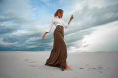 Young woman stands barefoot  in desert on sky background. Royalty Free Stock Image