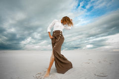 Young woman stands barefoot  in desert on sky background. Royalty Free Stock Photo