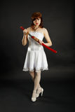 Young woman stands on black with a sword Stock Image