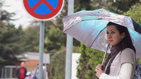Young woman stands at the bus stop. With an umbrella and waiting for the bus stock video footage