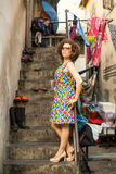 Young woman stands in the courtyard of the house in a poor neighborhood. Stock Photos