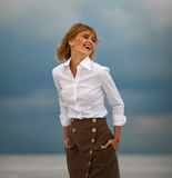 Young woman stands in desert on sky background. Portrait. Royalty Free Stock Image