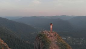 Young happy woman standing on the edge of a cliff. A young woman stands on the edge of a rock and raises her hands. Aerial shot, 4K stock video footage