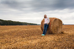 A young woman stands on the field, leaning on a sheaf of hay. Stock Photos