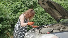 Young woman with parkinsonism stands infront of car and changes tools for car repairing. She takes out screwdriver. Young woman stands infront of car and stock footage