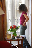 Young woman stands and looks out window at table. Next her is bouquet of red roses royalty free stock image