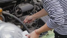 A young woman stands next to a car with an open hood and checks with a dipstick the oil level in the engine.