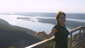 Young woman stands on the observation deck, looking at the camera and smiling. On the background of the Volga river. stock video footage