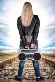 A young woman stands on the rail and holds the vintage tape recorder. royalty free stock photos