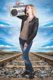 A young woman stands on the rail and listening to a vintage tape recorder. Woman stands on the rail and listening to a vintage tape recorder royalty free stock image