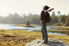 Young woman stands on rock in countryside, arms outstretched stock images