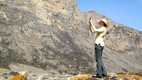 A young woman stands on a rock  and takes on the phone wildlife Royalty Free Stock Photo