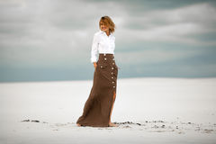 Young woman stands on sand in desert and smiles. Stock Photo