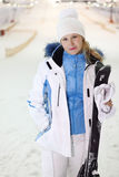 Young woman stands with skis and mittens Royalty Free Stock Photos