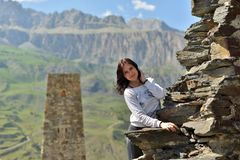 A young woman stands smiling near a ruined wall against a tower royalty free stock image