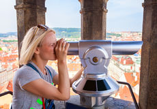 Young woman stands on top of clock tower and looks at Old Town in Prague using a telescope. Royalty Free Stock Photos