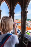 Young woman stands on top of clock tower and looks at Old Town in Prague using a telescope. Stock Images