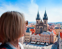 Young woman stands on top of clock tower and looks at Old Town Square in Prague Royalty Free Stock Photos