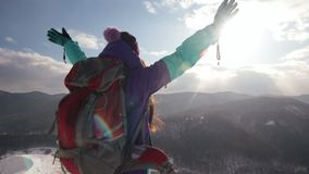 A happy woman stands on top of a mountain and enjoys the sunset. stock footage
