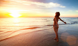 Young woman stands towards the sun on Sea beach during a amazing sunset. Stock Photo
