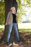 Young woman stands on a tree Stock Photography