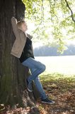 Young woman stands on a tree Royalty Free Stock Image