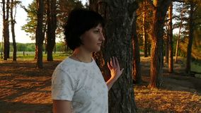 A young woman stands at a tree against the river and the forest. Silhouette of a woman at sunset. A young woman standing at a tree on the background of the stock video