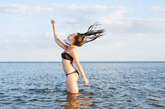 Young woman stands in water splashes. Young woman standing in the sea with splashes Stock Photo