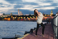 A young woman stands on the waterfront against evening the city Royalty Free Stock Photo