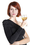 Young Woman Stares Holding Her Glass of Wine. Young woman in a black dress stares while holding a glass of white zinfandel wine Stock Photo