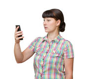 The young woman stares at the phone screen. Royalty Free Stock Images