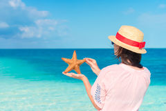 Young woman with starfish on white beach in the nature reserve Royalty Free Stock Photography