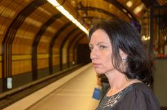 Young woman staring anxiously down the tracks. In a tube station as she waits for the train to arrive Royalty Free Stock Photography