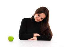Young woman staring at the apple. Young woman with long brown hair staring at the green apple Royalty Free Stock Image