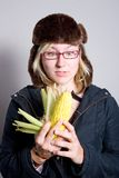 Young woman staring at cob of corn. Young woman staring at a cob of corn. Woman looks a bit dorky and artistic. She has a shocked/surprised look on her face Royalty Free Stock Images