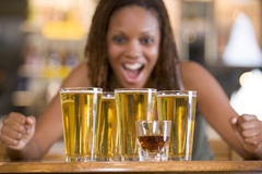 Young woman staring excitedly at a round of beers. In front of her Stock Photos