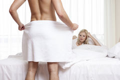 Young woman staring at naked man holding towel in bedroom Royalty Free Stock Images
