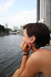 Young woman staring at the other side of the river. In Singapore Stock Images