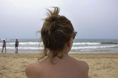 Young woman staring at the sea on the beach Royalty Free Stock Photography